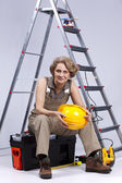 Senior woman sitting in a toolbox — Stock Photo
