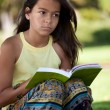 Stock Photo: Child reading a book at the park