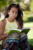 Child reading a book at the park — Stock fotografie