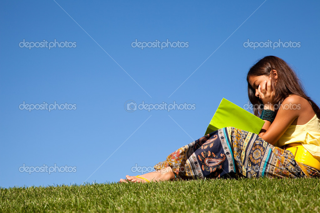 Young female child at the park reading a book — Stock Photo #8629500