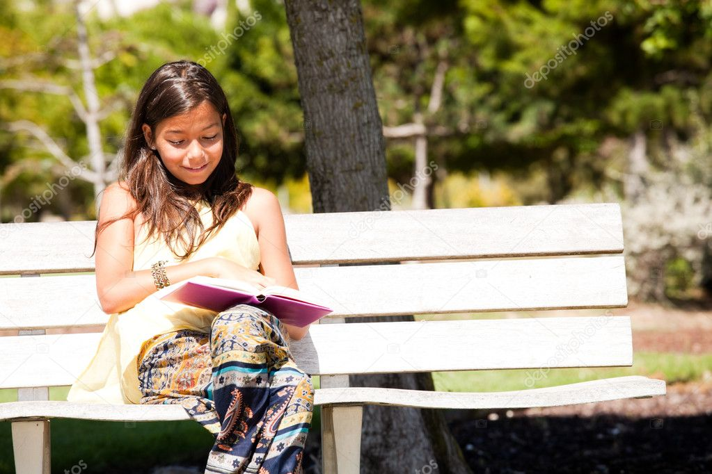 Young child at the park reading a book — Stock Photo #8629605