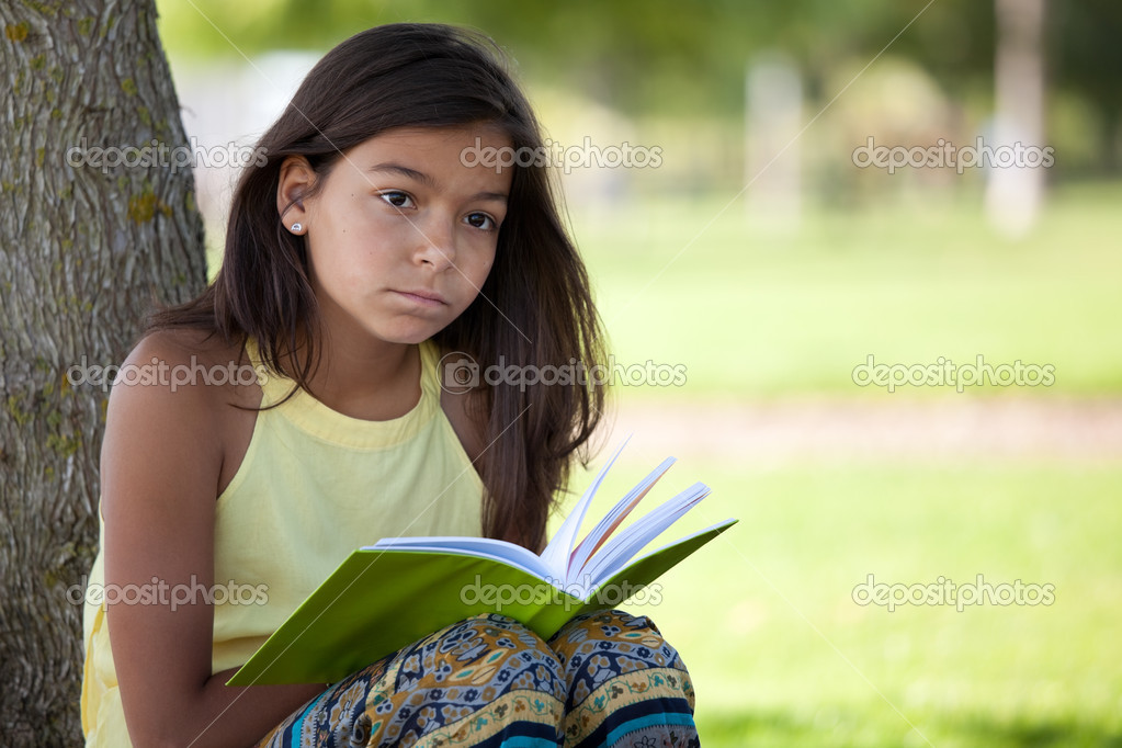 Little girl relaxing next to a tree reading a book — Foto Stock #8629611
