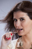 Woman biting chocolate — Stock Photo