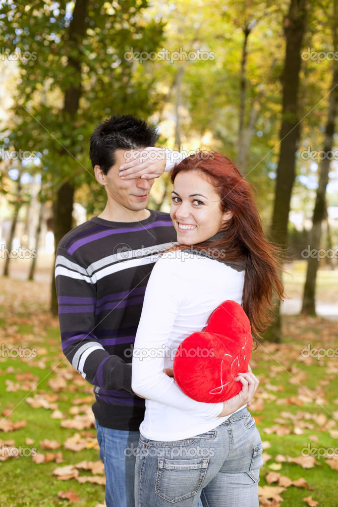 Woman covering the eyes to his boyfriend holding a red heart behind her back (selective focus with shallow DOF) — Stock Photo #8630295