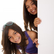 Sisters holding a blank billboard — Stock Photo #8659066