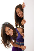 Sisters holding a blank billboard — Stock Photo