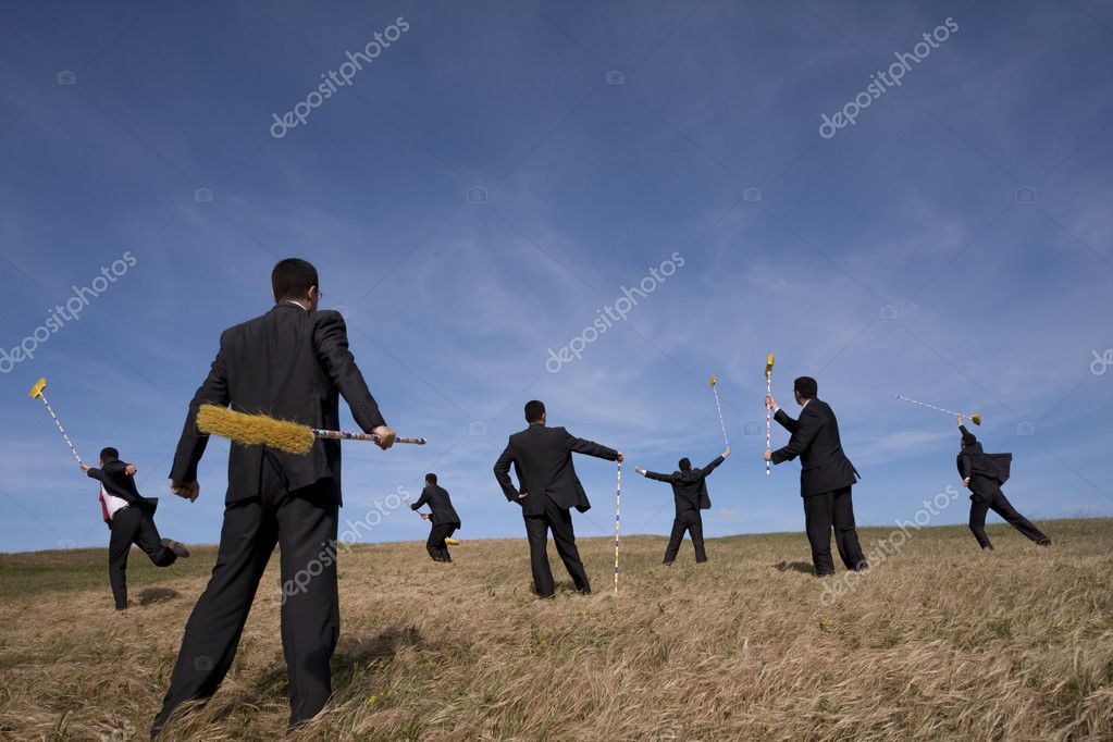 Businessman cleaning the field with a broom (some sharp, some with motion blur)  Stock Photo #8654480