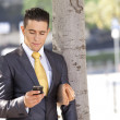 Businessman sending messages in his cellphone - Stock Photo