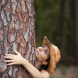 Stock Photo: Young woman embracing a tree