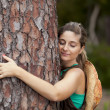 Young woman embracing a tree — Stock Photo