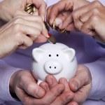 Hands inserting money in the piggybank — Stock Photo #8666817