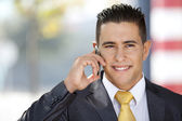 Happy businessman talking at his cellphone — Stock Photo