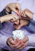 Handen invoegen van geld in de spaarpot — Stockfoto