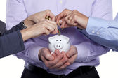 Hands inserting money in the piggybank — Stok fotoğraf