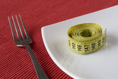 Fork, plate and a measure tape — Stock Photo