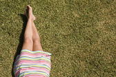 Woman legs at the grass — Stock Photo