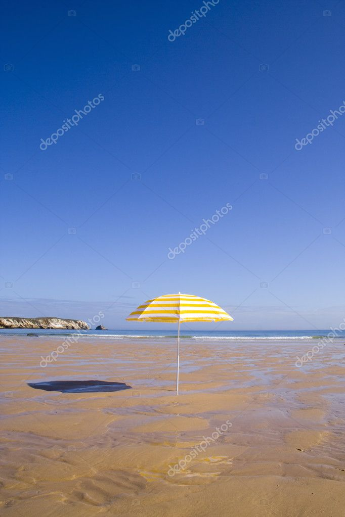 A summer scenic with a yellow parasol at the beach — Stock Photo #8673505