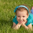 Cheerful smiling little girl on the green grass — Stock Photo