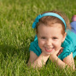 Cheerful smiling little girl on the green grass — Stock Photo #8136508