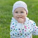 Smiling little girl in the polka dot jacket — Stock Photo