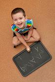 счастливый малыш учится писать на доске — Стоковое фото