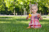 Holčička s hračkami v parku — Stock fotografie