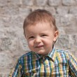 Portrait of a cute toddler against the stone wall — Stock Photo
