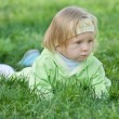 Thoughtful toddler is crawling in the green grass — Zdjęcie stockowe