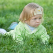 Thoughtful toddler is crawling in the green grass — Стоковая фотография