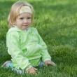 Portrait of a pretty little girl in green in the green grass — Stock Photo
