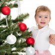 Happy little girl decorating a christmas tree — Stok fotoğraf