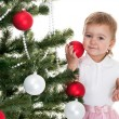 Toddler decorating christmas tree with red and white balls — Stock Photo
