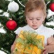 Toddler holding a christmas present at a new year tree — Stock Photo