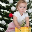 Toddler discovering a christmas present at a new year tree — Stock Photo