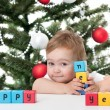 Cute toddler holding happy new year sign — Stock Photo