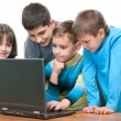 Stock Photo: Four children studying using a laptop