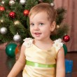 Little lady in gold at the christmas tree — Stock Photo