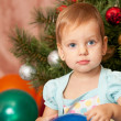 Little girl with big grey eyes at the fur tree — Stock Photo #8144235