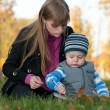 Mom teaches her son in the autumn park — Foto Stock