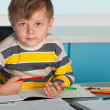 Serious little boy at the desk - Stock Photo