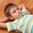 Portrait of thoughtful boy with big grey eyes lying on woo — Stockfoto #8144386