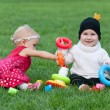 Portrait of two pretty little girls playing on the grass — Stock Photo