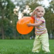 little girl playing with a ballon in the summer park — Stock Photo