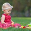 Pretty blond little girl is playing with toy pyramid on grass — Stock Photo