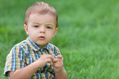 Closeup portrait of a thoughtful toddler against green grass — Stock fotografie