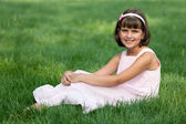 Girl in pink resting on the green grass — Stockfoto
