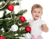 Happy little girl decorating a christmas tree — Stock Photo