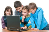 Four children studying using a laptop — Stock Photo