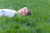Portrait of a smiling girl looking out of the green grass — Stock Photo