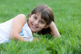 Closeup portrait of a pretty girl lying in the summer park — Stock Photo